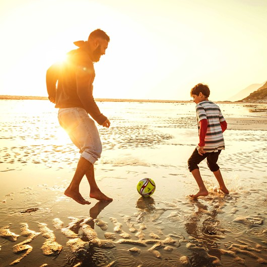 Adult and boy playing football on the beach