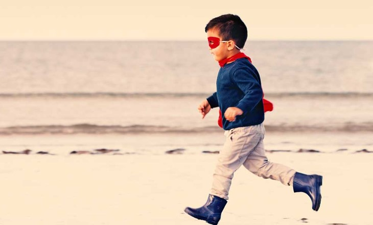Young boy dressed as super hero running on beach