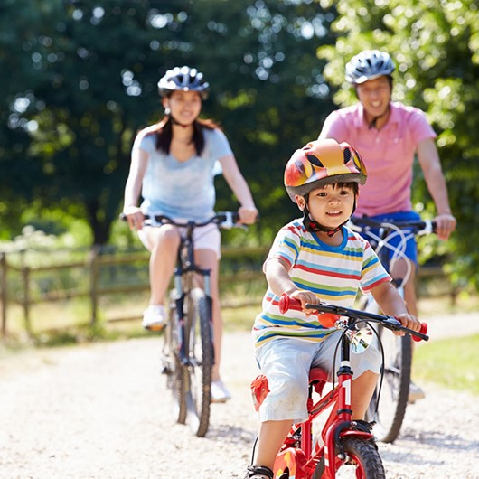 Family enjoying a bike ride on a gravel path