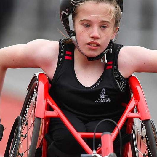 Girl pushing a racing wheelchair down the track