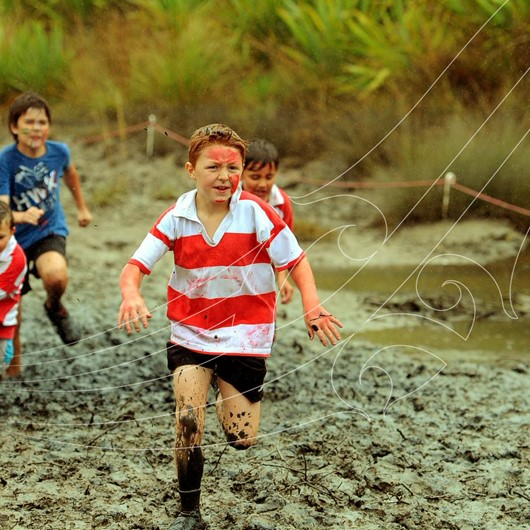 Boys running on a very muddy track