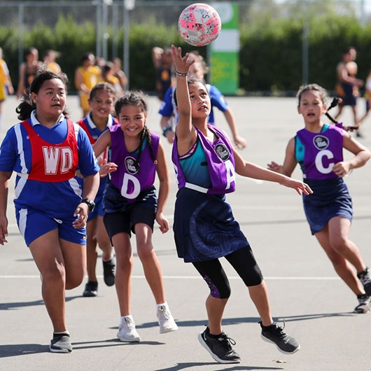 Girls in purple and red bibs playing netball