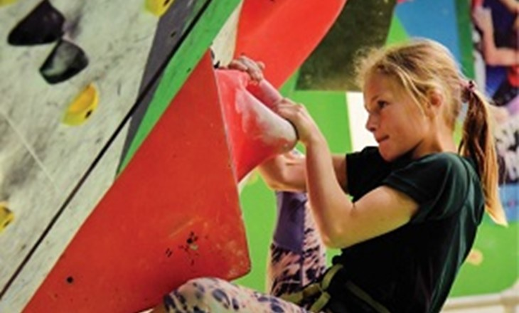 Girl scaling a climbing wall