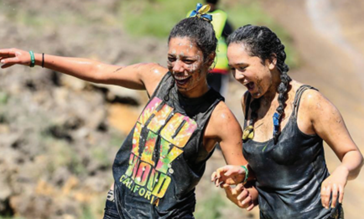 Two girls partaking in a muddy challenge