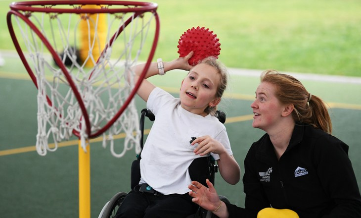 Girl in wheelchair shooting a basket as helper watches
