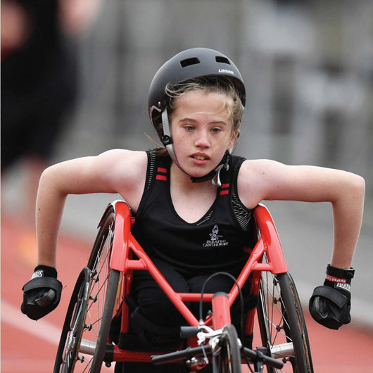 Girl racing a wheelchair around a track