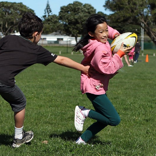 Boy tags a girl during a game of touch rugby