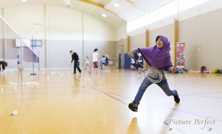 Muslim girl playing badminton in a gym