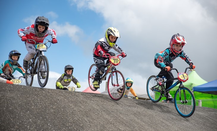 A group of kids in a BMX race coming over a hill
