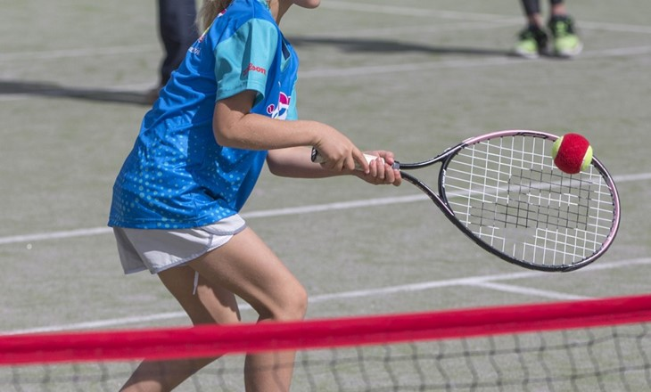 young girl hitting a tennis ball on a tennis court