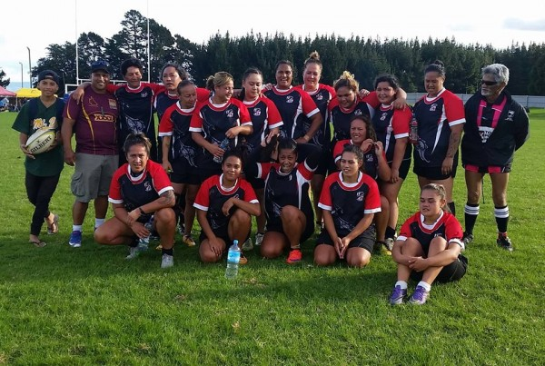 a girls rugby team posing for a photo after a game