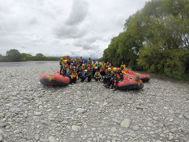 Group pose on river bank with inflatables